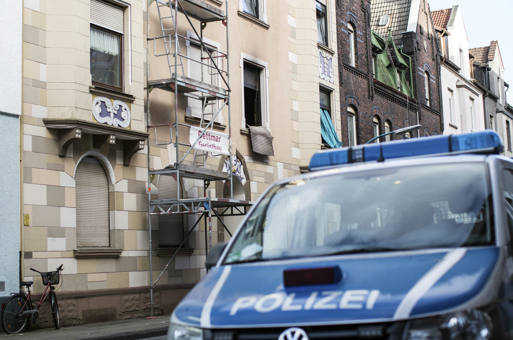 A police vehicle stands in front of a destroyed roller shutter that hangs from a burnt out apartment window in Herne, western Germany, ...