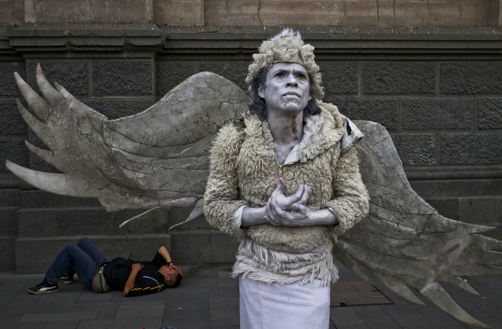In this Tuesday, March 7, 2017 photo, a street performer dressed as an angel holds still, waiting to move only when a pedestrian tips h...