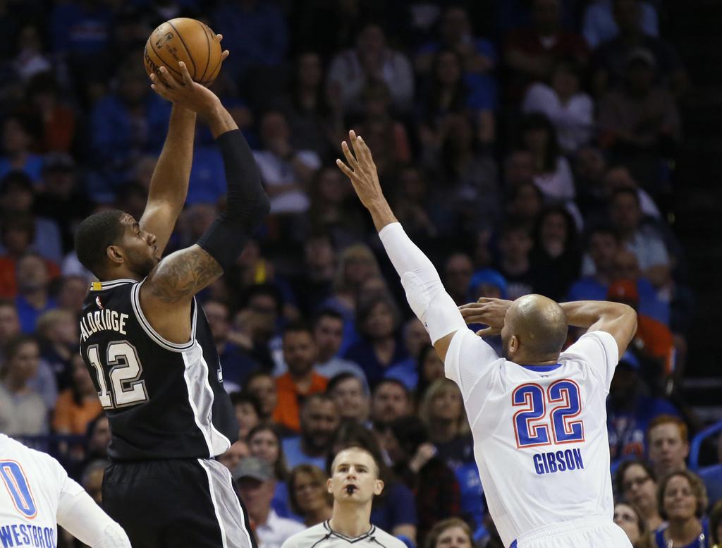 San Antonio Spurs forward LaMarcus Aldridge (12) shoots over Oklahoma City Thunder forward Taj Gibson (22) during the first quarter of ...