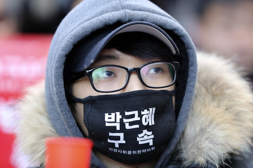 A protester wearing a mask, attends during a rally calling for impeachment of President Park Geun-hye near the Constitutional Court in ...