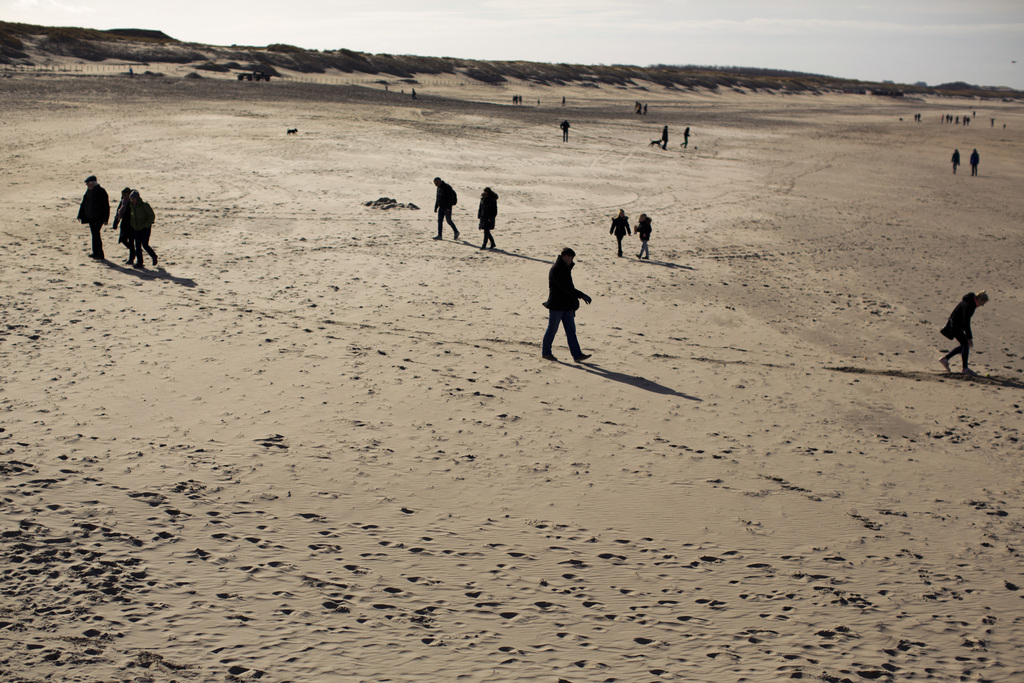 In this Sunday, March 5, 2017 photo, people walk along the beach in The Hague, The Netherlands. Of The Netherlands' 17 million people, ...