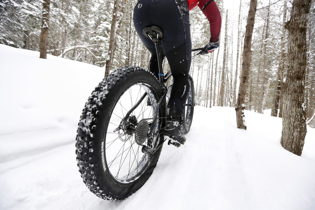 In this Saturday, Feb. 11, 2017 photo a fat tire bicyclist rides on a cross country ski trail during a race at the Sugarloaf ski resort...