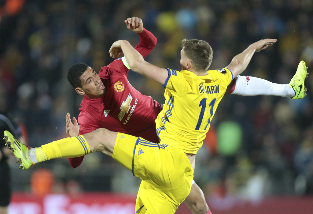 Manchester United's Chris Smalling, left, and Rostov's Aleksandr Bukharov fight for the ball during the Europa League round of 16 first...