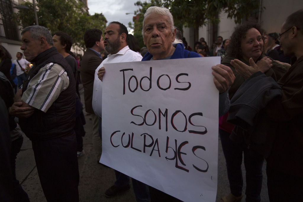 """A man holds a sign that reads in Spanish: """"We're all guilty"""" during a protest outside the presidential house to demand justice for the ..."""