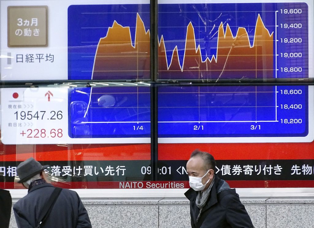 A man looks at an electronic stock board of a securities firm showing the chart of Tokyo's Nikkei 225 stock index movement in the past ...