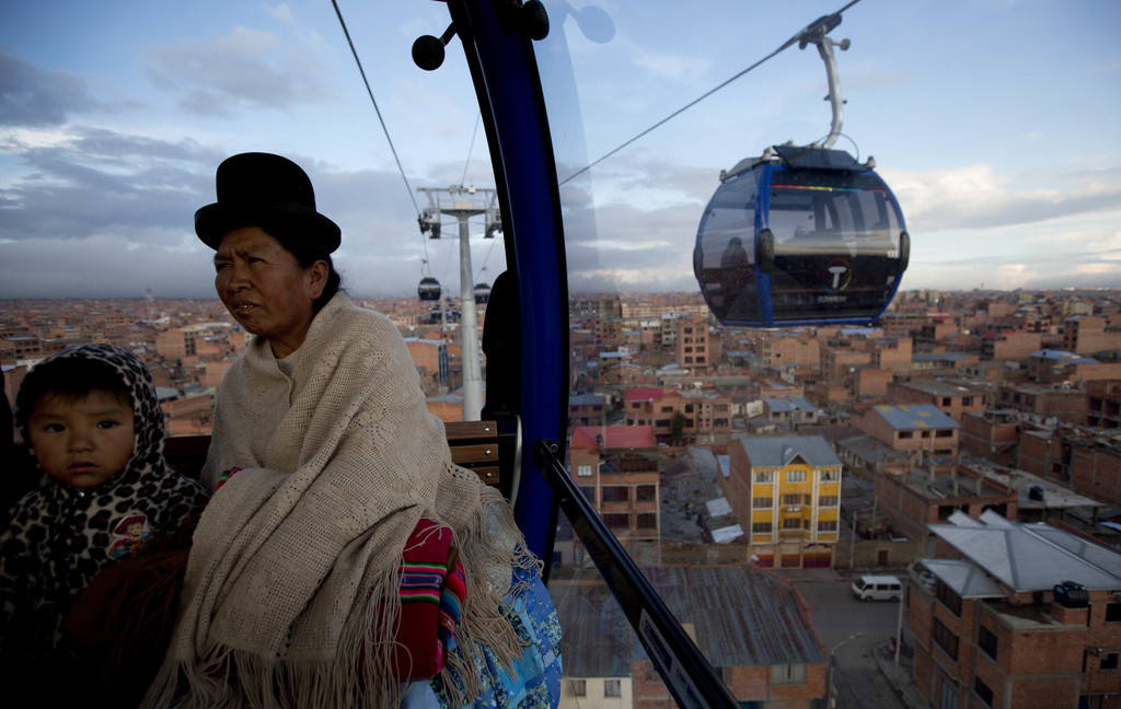 In this Friday, March 3, 2017 photo, a woman and a child ride a cable car that interconnects the city El Alto, Bolivia. The cable car s...