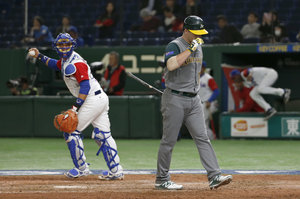 Australia's last batter Brad Harman leaves for his dugout after getting struck out looking as Cuba's catcher Frank Morejon celebrates t...