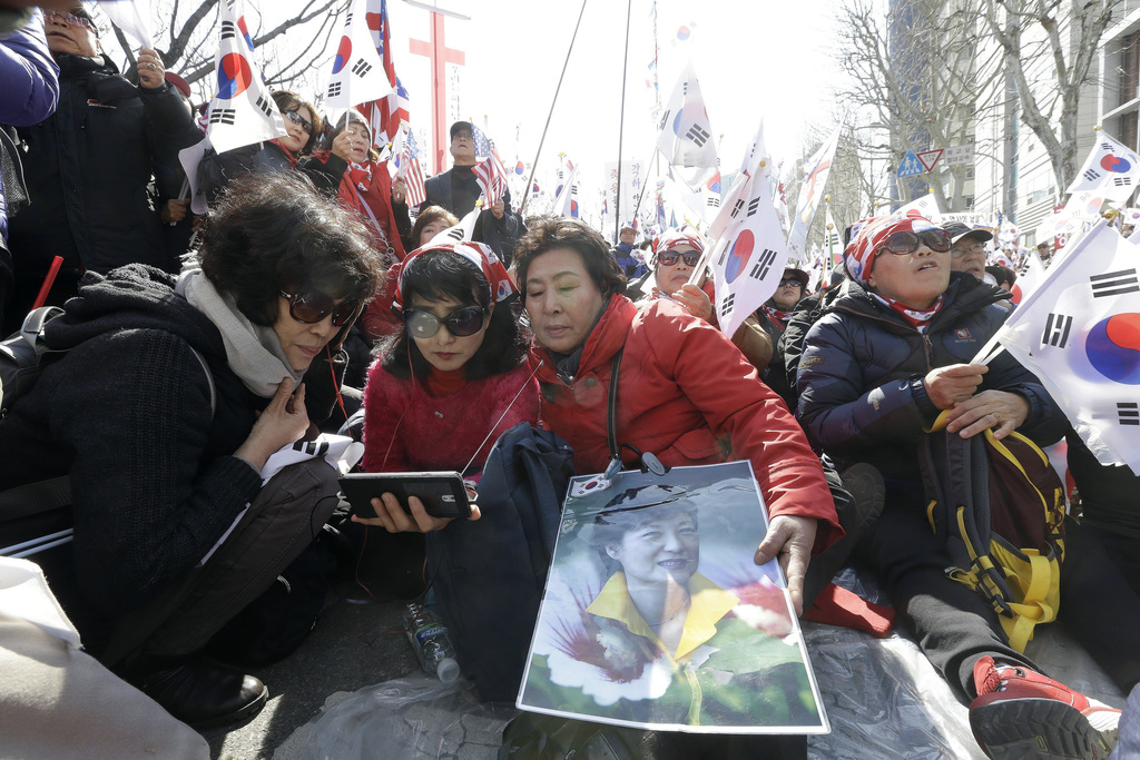 Supporters of South Korean President Park Geun-hye watch a broadcast live of a Constitutional Court decision on a smart phone during a ...