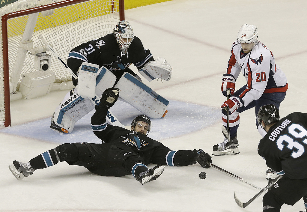 San Jose Sharks defenseman Dylan DeMelo, bottom, reaches for the puck in front of goalie Martin Jones (31) and Washington Capitals cent...