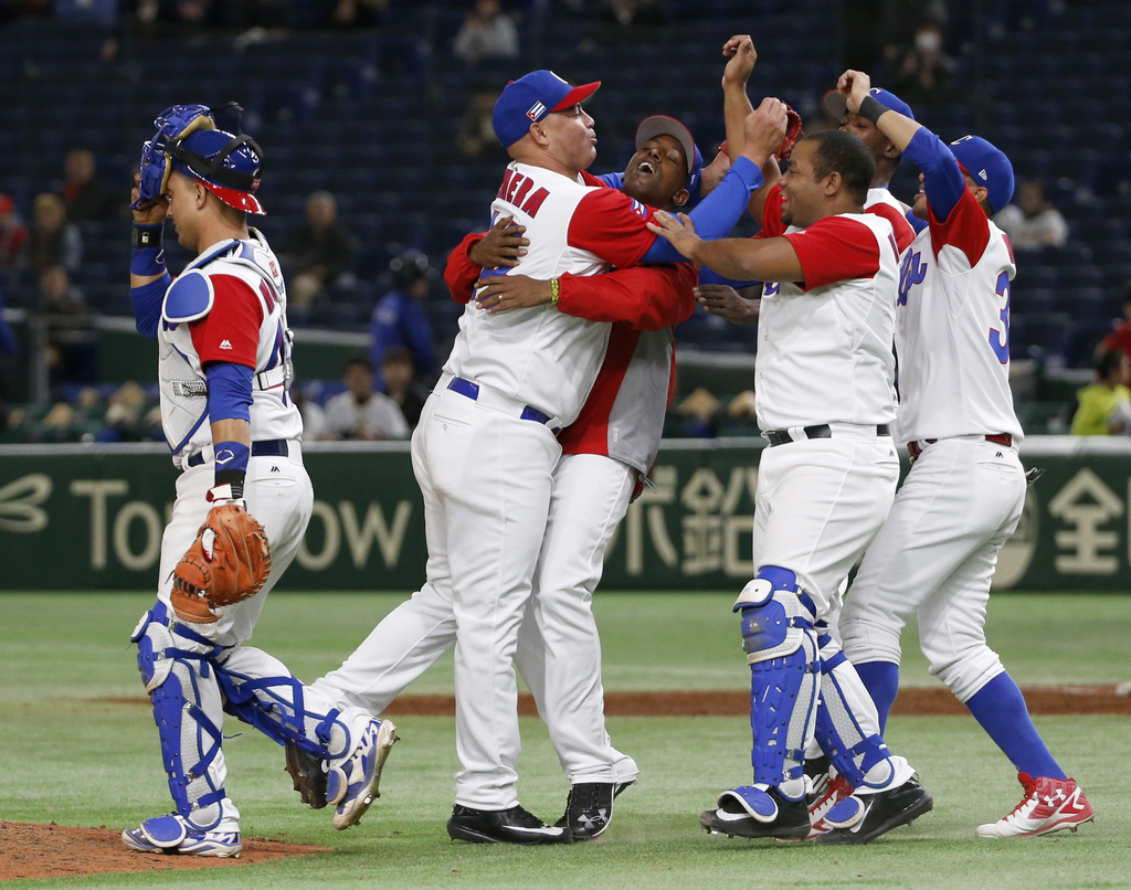 Cuba's closer Miguel Lahera, second from left, celebrates with teammates after their 4-3 win over Australia in their first round game o...