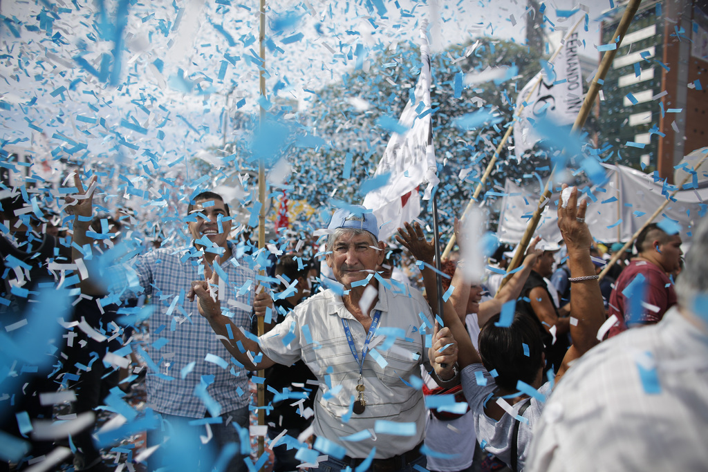 In this Tuesday, March 7, 2017 photo, confetti in the colors of the Argentine flag rain on demonstrators during a labor march in Buenos...