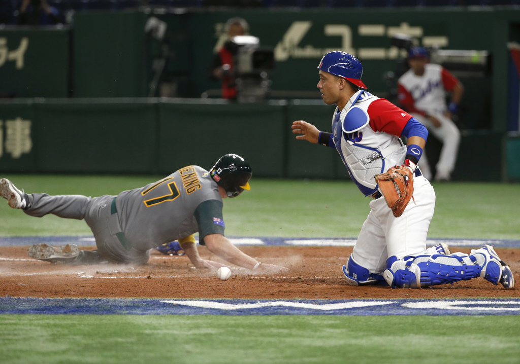 Australia's Mitch Dening (17) scores on Logan Wade's single as Cuba's catcher Frank Morejon drops the ball during the fifth inning of t...