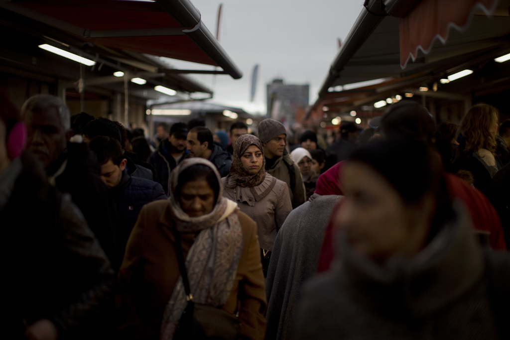 In this Saturday, March 4, 2017 photo, people walk along street stalls at a fruit market in The Hague, The Netherlands. In The Hague's ...