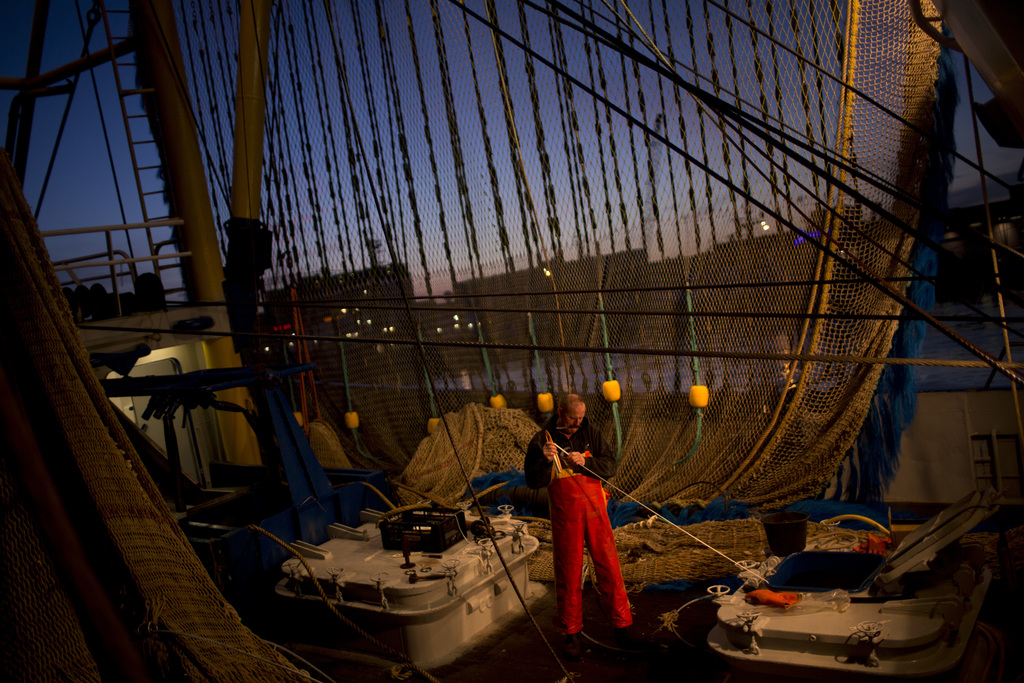 In this Friday, March 3, 2017 photo, a fisherman works on his ship fixing a fishing net at the port in The Hague, The Netherlands. The ...