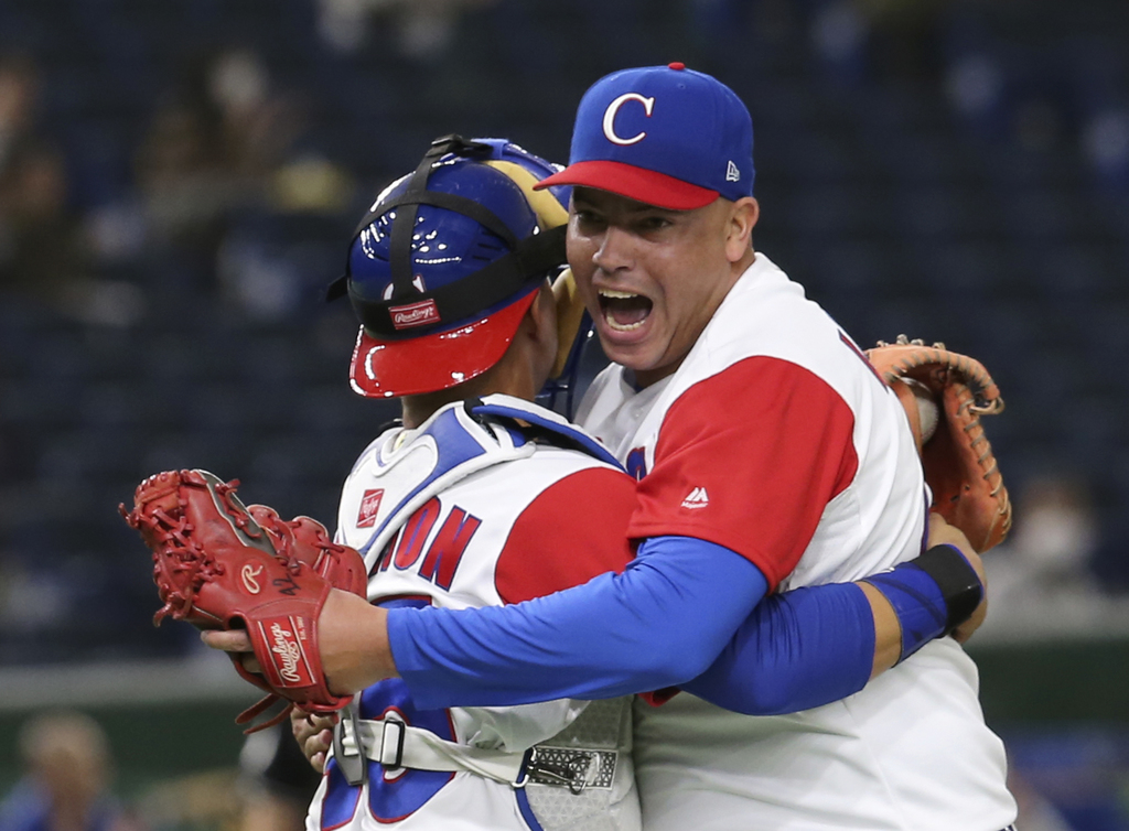 Cuba's closer Miguel Lahera, right, hugs catcher Frank Morejon after their 4-3 win over Australia in their first round game of the Worl...