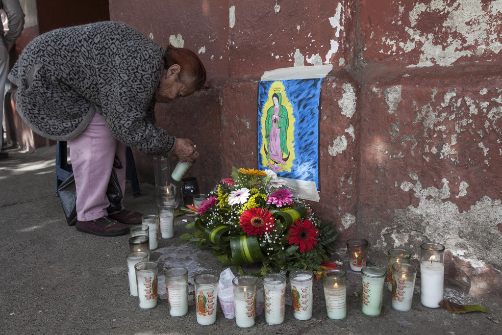 Consuelo Garrido lights a candle in remembrance of the victims of a fire at a youth shelter, at a makeshift memorial outside the morgue...