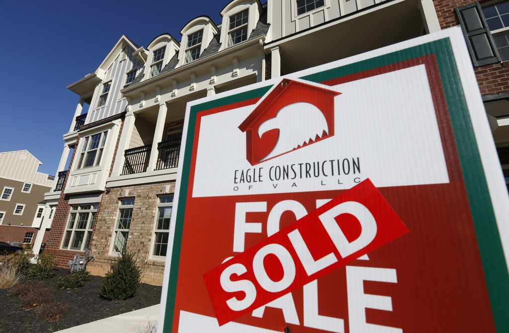 FILE - In this Jan. 8, 2015, file photo, a sign with a sold sticker is posted in front of a row of new town homes in Richmond, Va. On M...