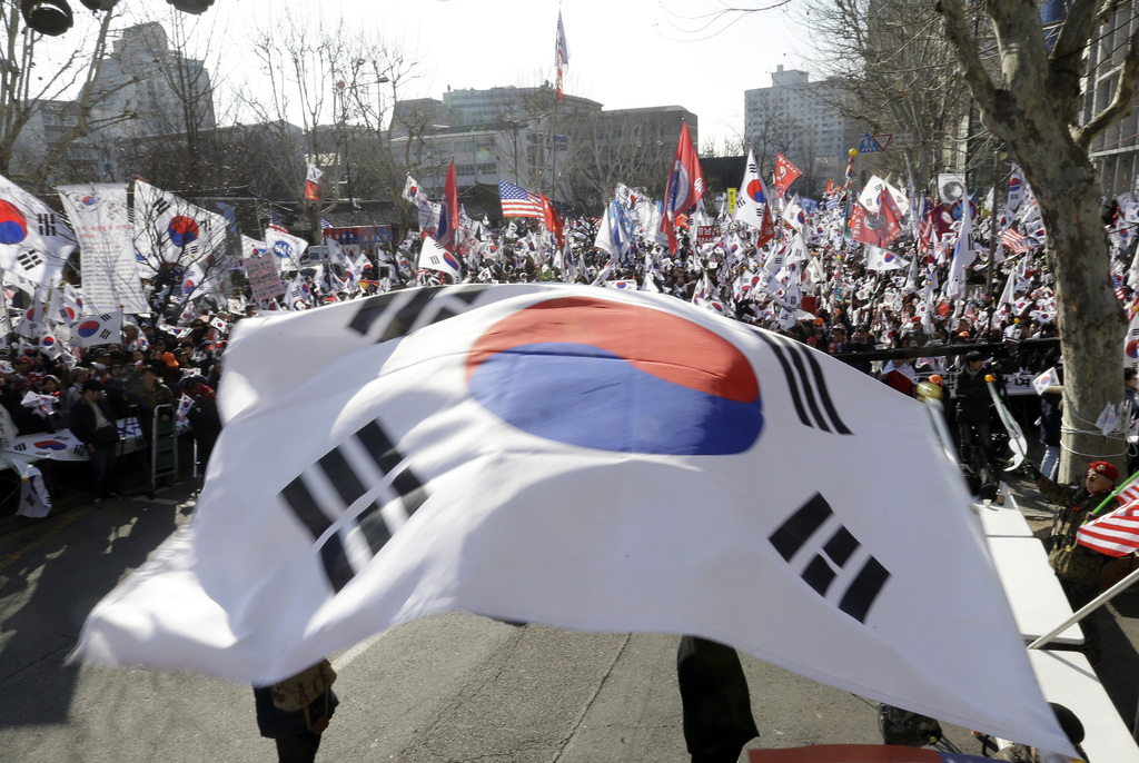 Supporters of South Korean President Park Geun-hye wave national flags during a rally opposing her impeachment near the Constitutional ...