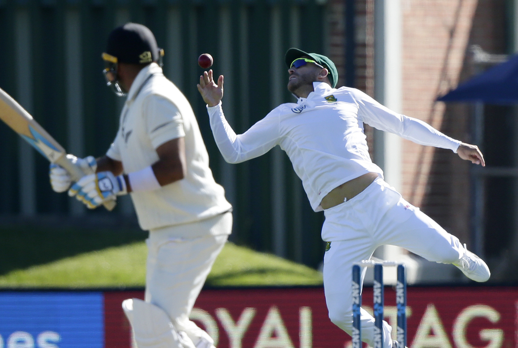 South Africa's Faf du Plessis takes a catch to dismiss New Zealand's Jeetan Patel, left, during the first cricket test at University Ov...
