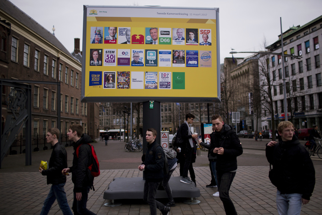 In this Friday, March 3, 2017 photo, people walk by a billboard showing the candidates for the Parliamentary elections scheduled for Ma...