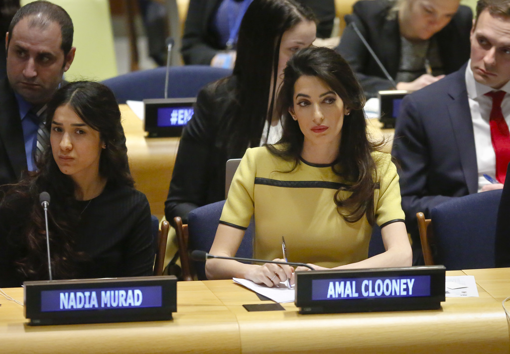 Human rights lawyer Amal Clooney, right, and her client Nadia Murad, left, a human rights activist and Yazidi genocide survivor, listen...
