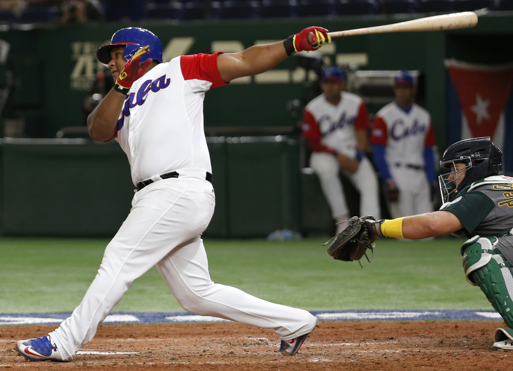 Cuba's Alfredo Despaigne watches the flight as he hits a grand slam off Australia's pitcher Lachlan Wells during the fifth inning of th...