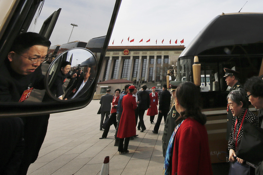 Delegates disembark from buses as they arrive for a plenary session of the Chinese People's Political Consultative Conference (CPPCC) h...