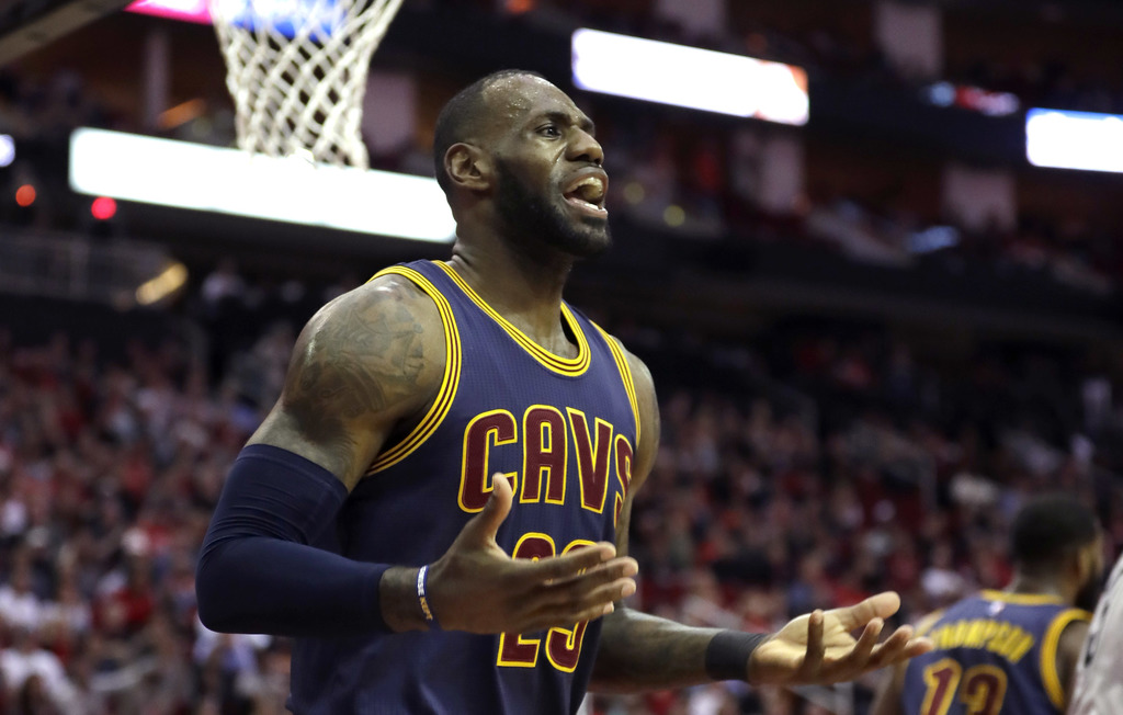 Cleveland Cavaliers' LeBron James reacts after being called for a foul against the Houston Rockets during the first quarter of an NBA b...