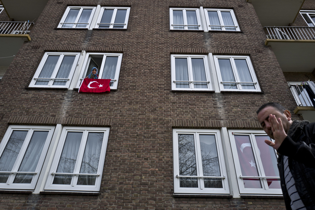 A man, right, gestures while walking by an apartment building decorated with Turkish flags in Amsterdam, Netherlands, Monday, March 13,...