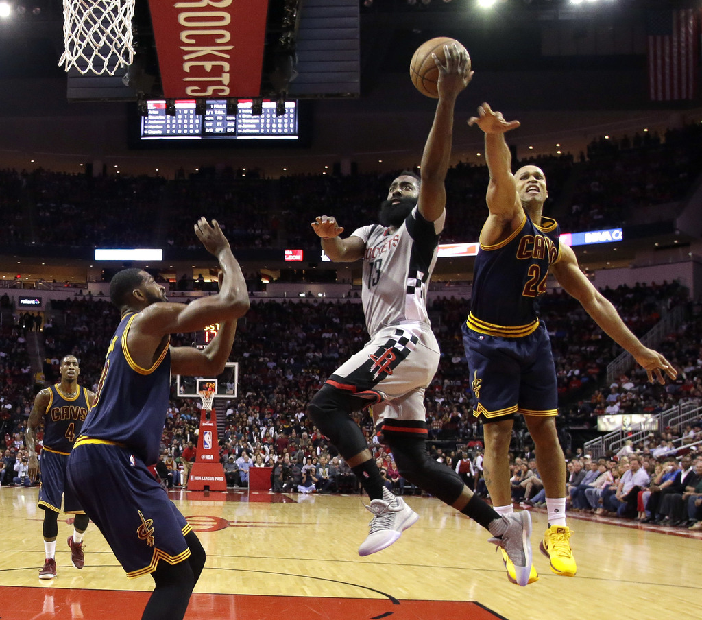 Houston Rockets' James Harden (13) goes up for a shot as Cleveland Cavaliers' Richard Jefferson (24) and Tristan Thompson, left, defend...