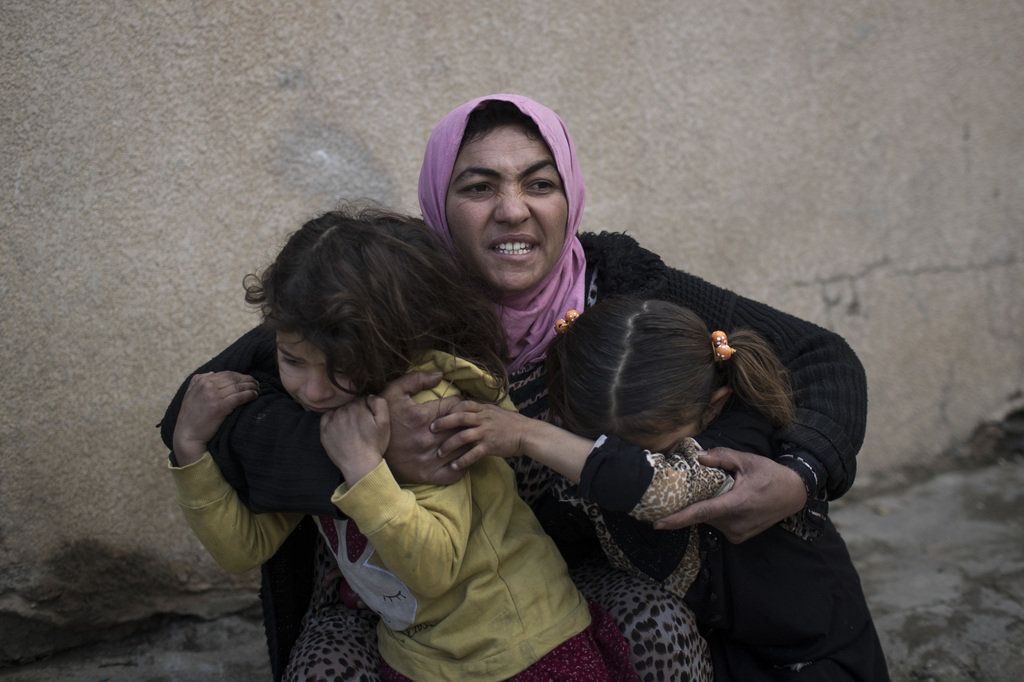 FILE - In this Tuesday, March 14, 2017 file photo, a woman holds her daughters as gunshots are heard in a neighborhood recently liberat...