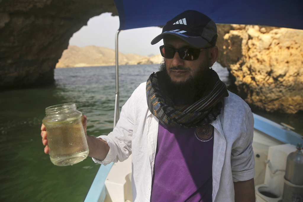 In this Feb. 26, 2017 photo, marine biologist Khalid al-Hashmi, 50, holds a jar with a sample of an algae blooming in the Gulf of Oman....