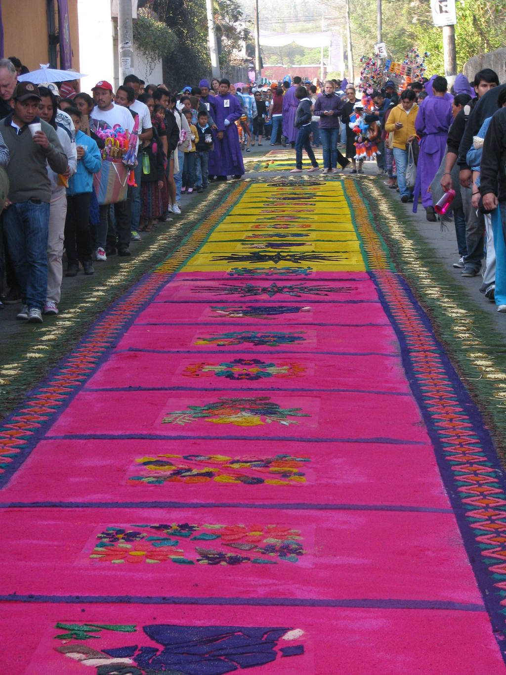 This March 22, 2015 photo shows a block-long, intricately designed carpet made of colored sawdust on a cobblestone street in Antigua, G...