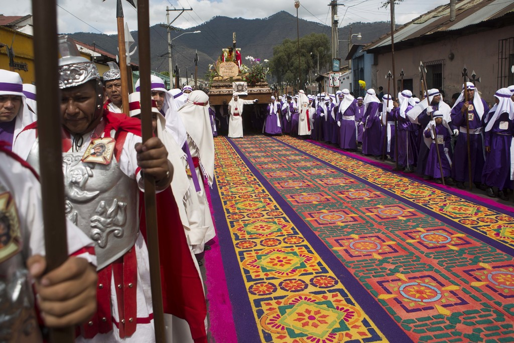 FILE - In this April 3, 2015, file photo, a street decoration made from dyed sawdust lays intact before a Good Friday procession walks ...