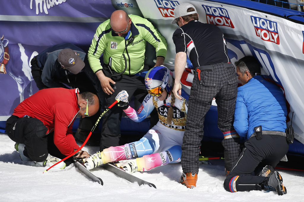 People help United States' Lindsey Vonn after she slid into a barrier following a run at the women's World Cup downhill ski race Wednes...