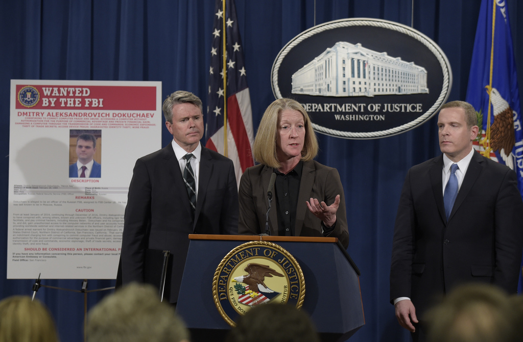 Acting Assistant Attorney General Mary McCord, center, accompanied by U.S. Attorney for the Northern District Brian Stretch, left, and ...