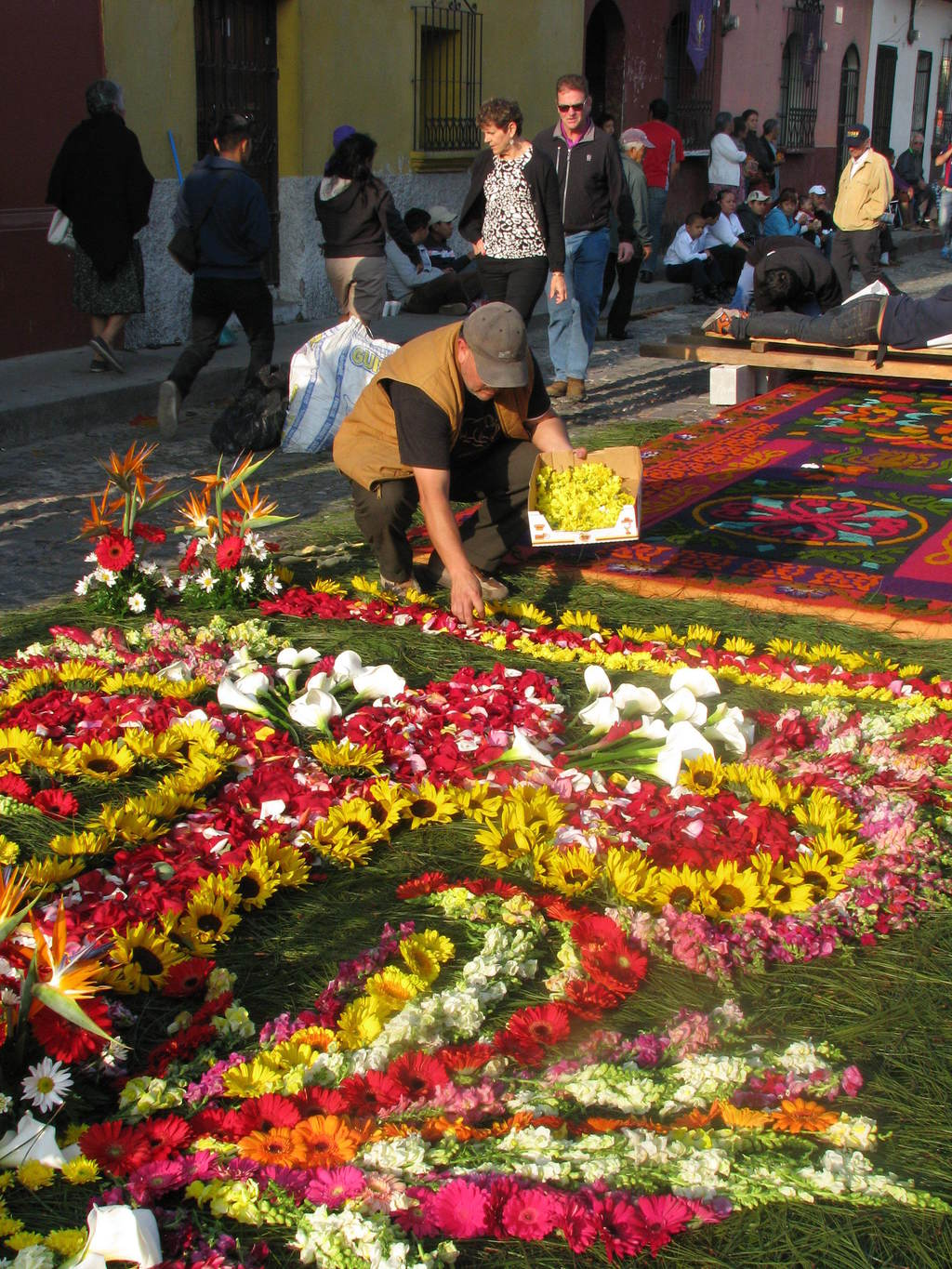 This March 22, 2015 photo shows a man creating a carpet with tropical flowers and rose petals in honor of the first of the elaborate Ea...