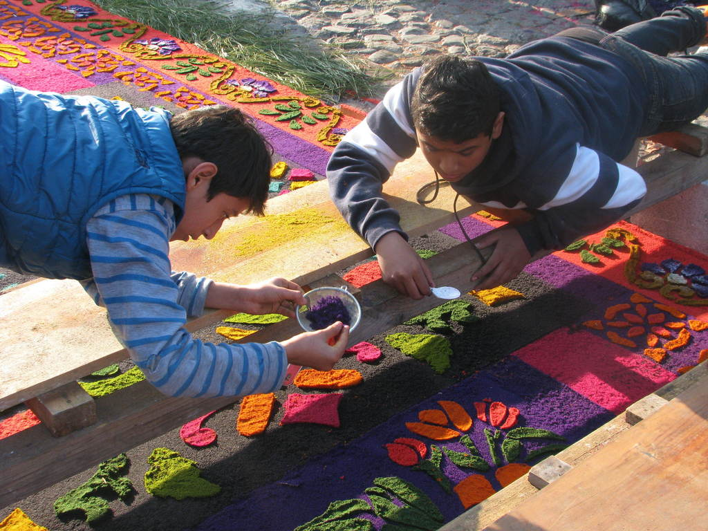 This March 22, 2015 photo shows two young men putting the finishing touches on an elaborate sawdust pattern created on top of a cobbles...
