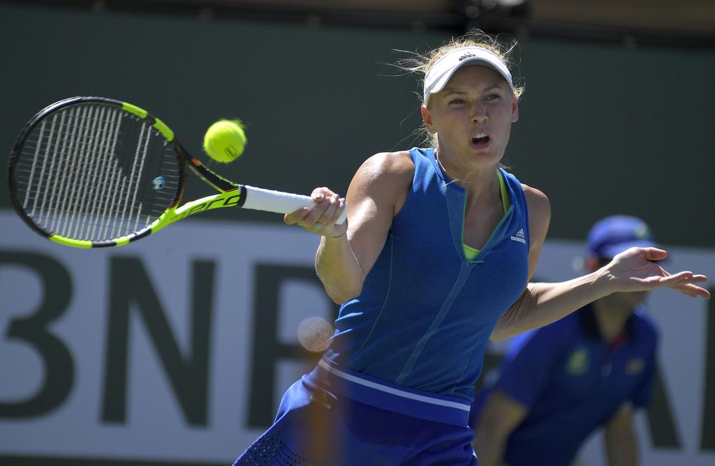 Caroline Wozniacki, of Denmark, returns a shot to Kristina Mladenovic, of France, at the BNP Paribas Open tennis tournament, Thursday,