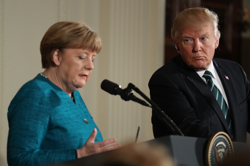 President Donald Trump looks to German Chancellor Angela Merkel as she speaks during a joint news conference in the East Room of the Wh...