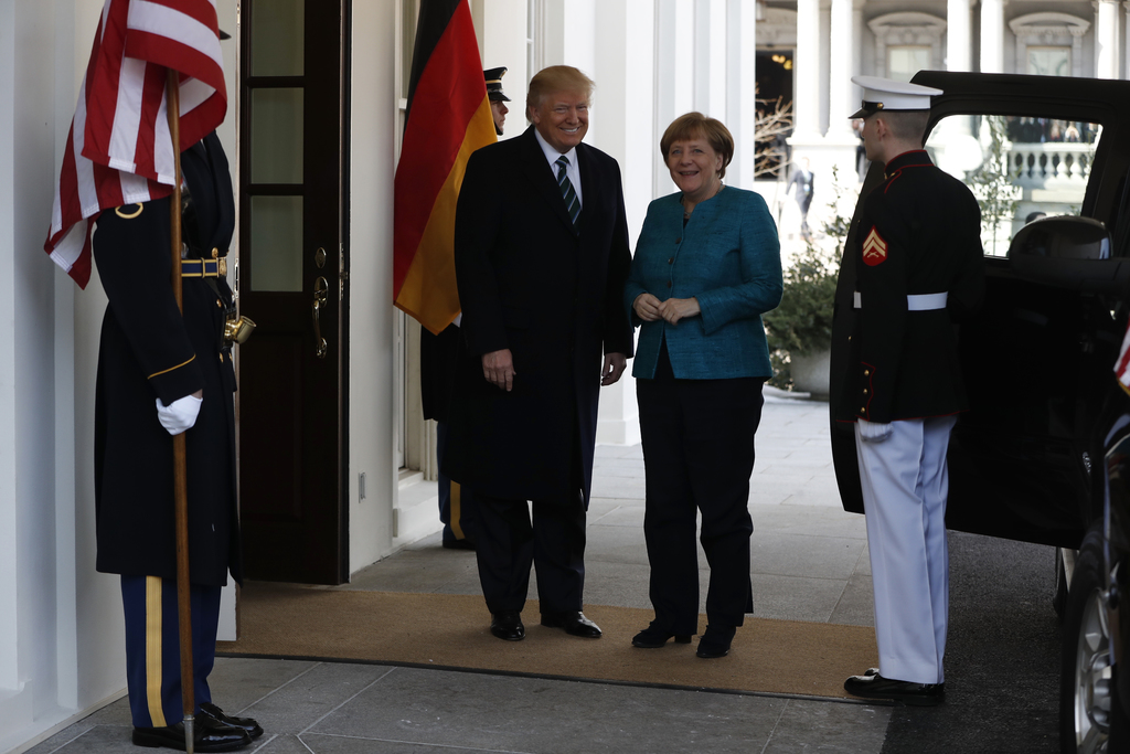 President Donald Trump and German Chancellor Angela Merkel pause for photographs as Merkel arrives outside the West Wing of the White H...