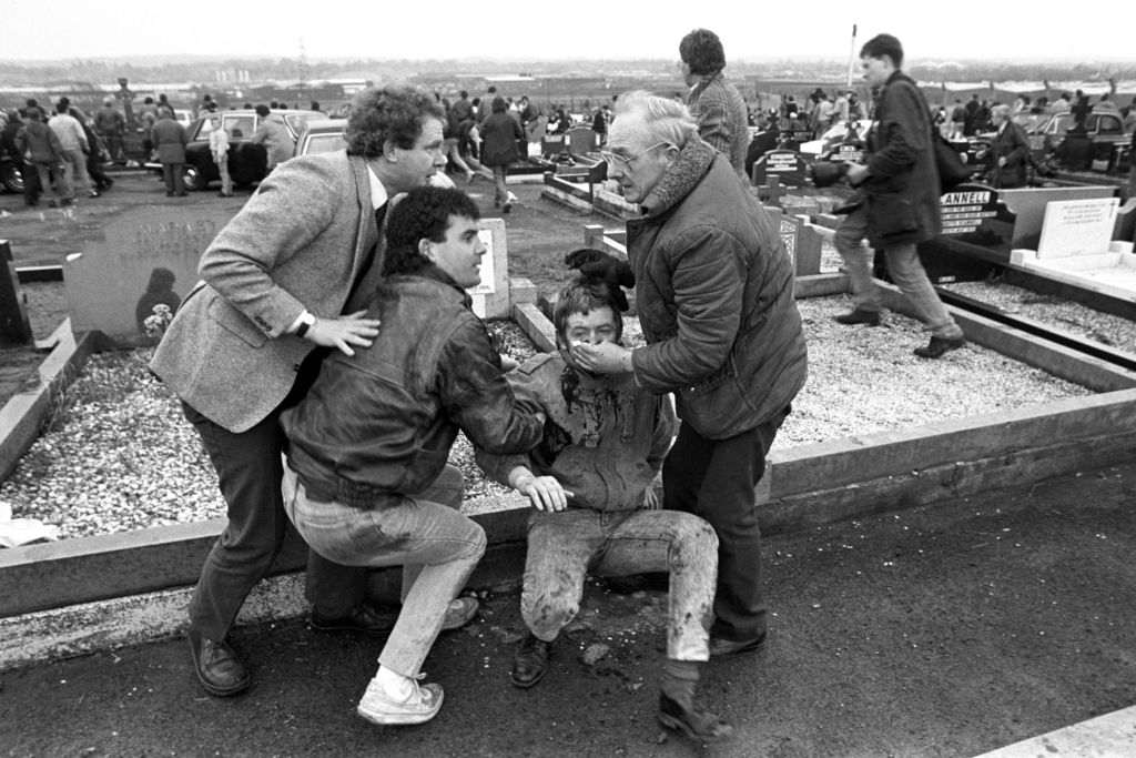 FILE - In this March 16, 1988 file photo an injured man is aided by mourners, including Sinn Fein vice president Martin McGuinness, lef...