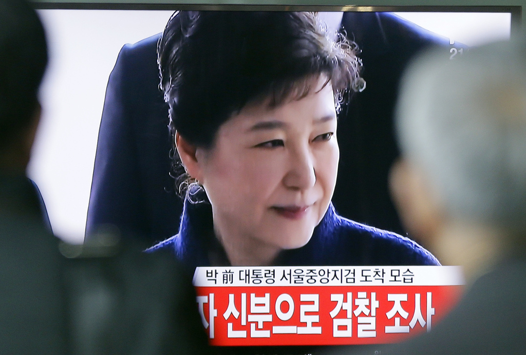 People watch a TV news program showing South Korean ousted President Park Geun-hye's arrival at prosecutors office, at Seoul Railway St...