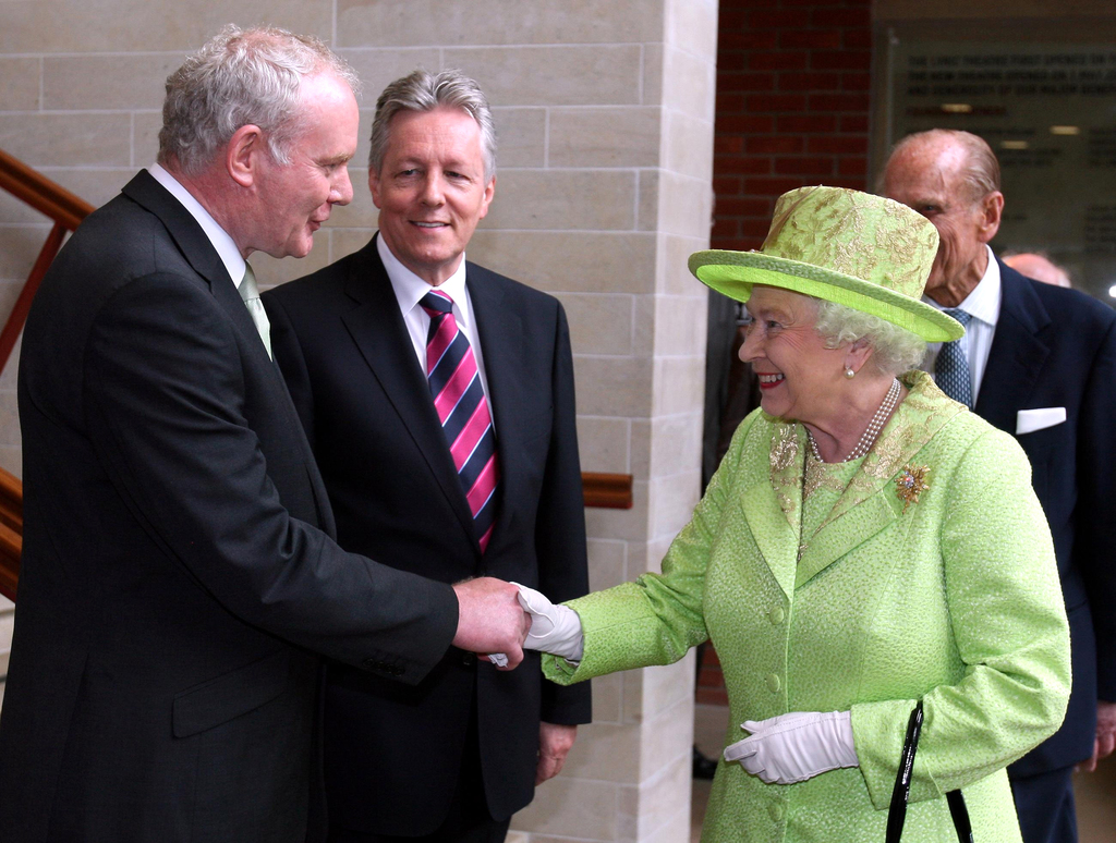 FILE - In this June 27, 2012 file photo Britain's Queen Elizabeth II shakes hands with Northern Ireland Deputy First Minister and forme...