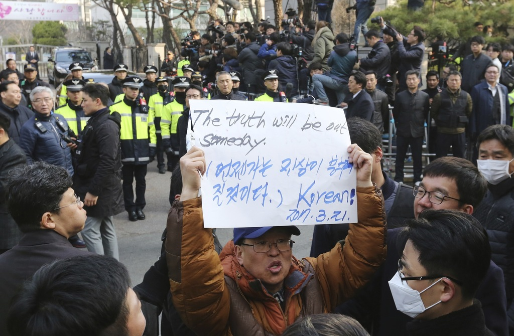 A supporter of ousted South Korean President Park Geun-hye holds up a paper to oppose her impeachment in front of her private home in S...
