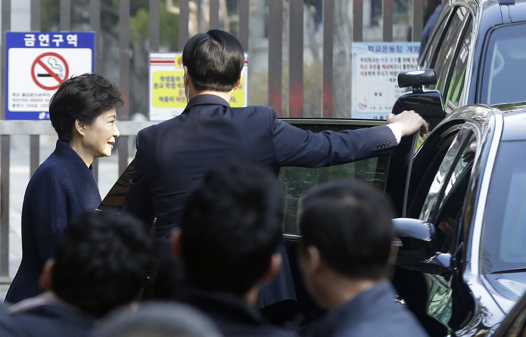 Ousted South Korean President Park Geun-hye, left, gets into a car to leave from her private home to prosecutors office in Seoul, South...