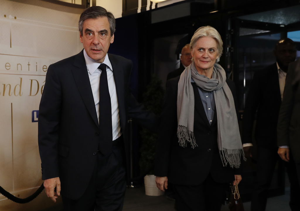 Conservative presidential candidate Francois Fillon, left, and his wife Penelope arrive for a television debate at French TV station TF...