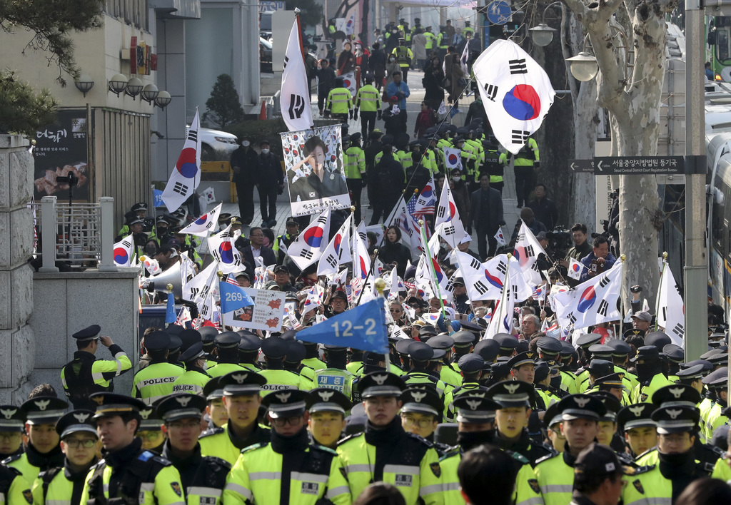 Supporters of South Korean ousted President Park Geun-hye wave national flags and picture of Park outside of a prosecutors' office in S...