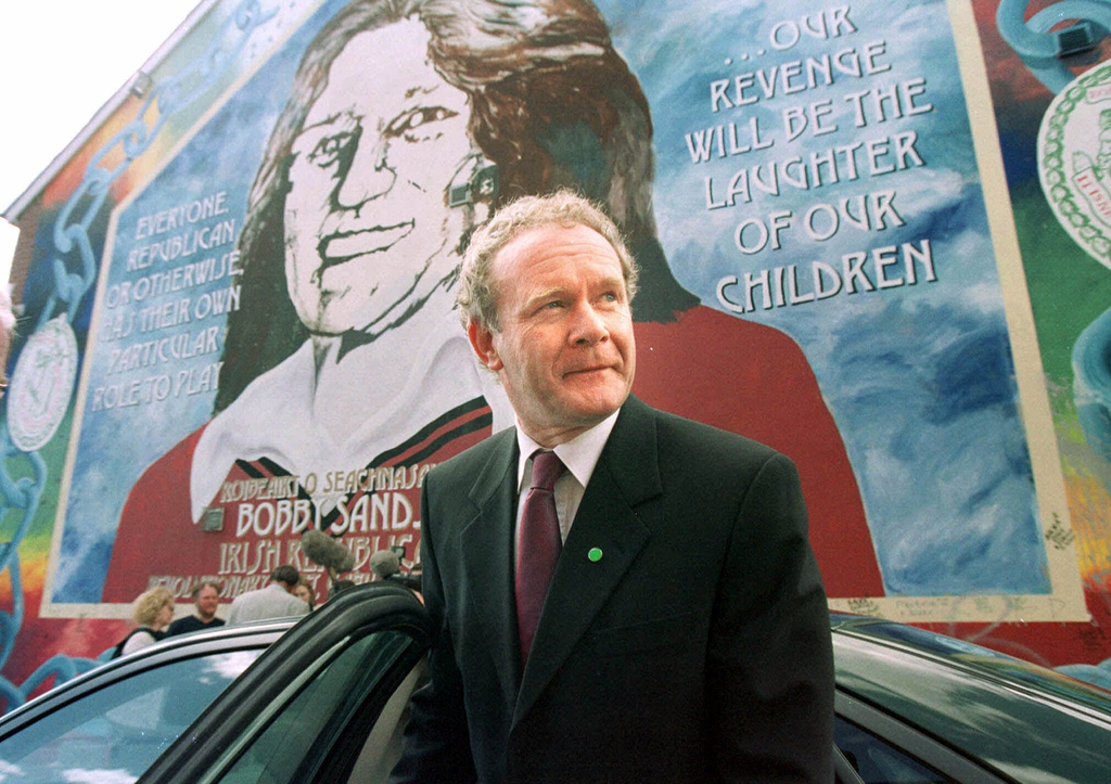FILE - In this April 30, 2001 file photo Martin McGuinness, leaves a Belfast news conference in front of a mural of Bobby Sands on the ...