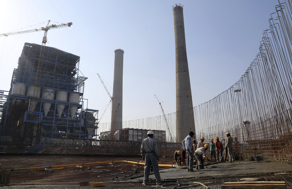 FILE- In this Feb. 24, 2015 file photo, workers lay cement to build a concrete structure at the under-construction coal-fired power pla...